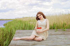 Girl with long hair in water in summer with strawberries Royalty Free Stock Photos