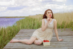 Girl with long hair in water in summer with strawberries Royalty Free Stock Image