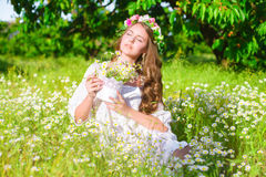 The girl with long hair wearing a crown of daisies on the field Stock Photography
