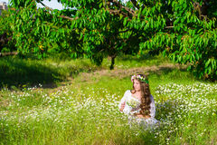 The girl with long hair wearing a crown of daisies on the field Royalty Free Stock Images