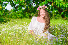 The girl with long hair wearing a crown of daisies on the field Stock Photo