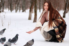 Girl with long hair wrapped in a blanket and doves in winter par Royalty Free Stock Images