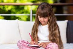 Girl with long hair writing at notepad Stock Image
