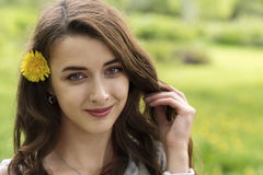 Girl with long hair and yellow dandelion Royalty Free Stock Photo