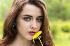 Girl with long hair and yellow dandelion Royalty Free Stock Photos