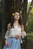 A girl with long hair and a yellow dandelion is standing by the trunk of a tree Royalty Free Stock Photos