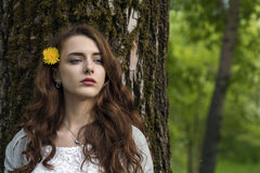 A girl with long hair and a yellow dandelion is standing by the trunk of a tree Stock Photography
