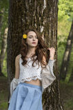A girl with long hair and a yellow dandelion is standing by the trunk of a tree Stock Image