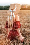 A girl with long hairs standing in wheat field is smiling happy. A man gives flowers behind his back. Concept of love stock photography