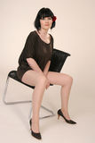 Girl with long legs. Sitting on a chair Stock Photo