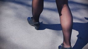 A girl with long legs in black shiny pantyhose and black shoes walks along the asphalt stock video footage