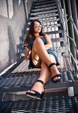 Girl with long legs sitting on metal platform Stock Photos