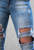 Girl with long legs wearing fashionable torn jeans trousers Stock Image