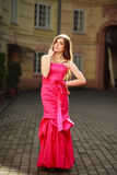 Girl in long pink dress on street of old town. Girl in luxurious long pink dress on street of old town Royalty Free Stock Photos