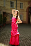 Girl in long pink dress on street of old town Royalty Free Stock Photo