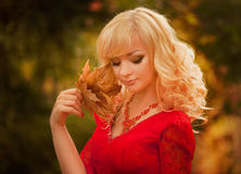 Girl in a long red dress  in the autumn forest Royalty Free Stock Photo