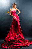 Girl in a long red dress holds Royalty Free Stock Images