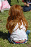Girl with long red hair. Back of a caucasian white little girl with beautiful long red hair sitting in the grass on the lawn and watching other kids on the royalty free stock photos