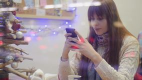 A girl with long red hair and a long bang in the cafe window writes a message typing text in a smartphone.  stock footage