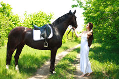 A girl in a long white dress with a horse on a country road Stock Images