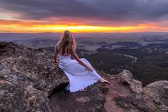 Girl in long white dress watching the sunset at Mt Blackheath stock photo