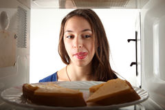 Girl look on the butter broads and lick. Girl lick to the sandwich. Through microwave oven view Royalty Free Stock Images