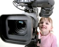 Girl look in the camcorder. The little girl in pink dress look to the finder of dv-camcorder Stock Image