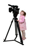 Girl look in the camcorder. The little girl in pink dress look to the finder of dv-camcorder Stock Photography