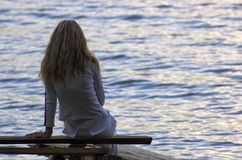 Girl look at lake. Girl siting in the pier wathing a water in lake Stock Images