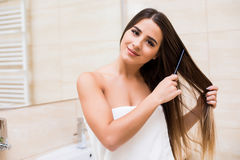 Girl look in mirror in bathroom. And make her hair royalty free stock photo