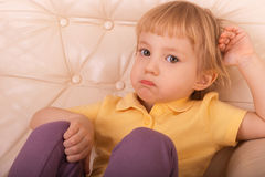 Girl with a look of resentment. Little girl sitting on couch with a look of resentment Royalty Free Stock Photos