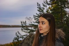 The girl look in the side against the background of a forest lake royalty free stock image