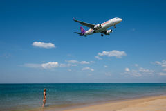 Girl look at Thai smile airline landing at Phuket Stock Images