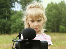 Girl look to the finder of camcorder royalty free stock photography