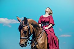 The girl looked up and looked at the sky. Beautiful girl in a long red dress riding a brown horse against a blue sky. The girl looked up and looked at the sky royalty free stock image