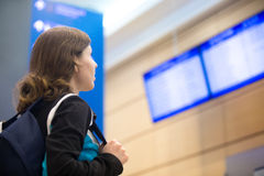 Girl looking at airport flight information board Royalty Free Stock Image