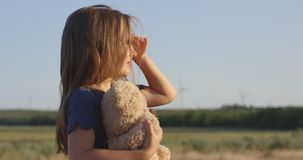 Girl looking around in field stock video footage