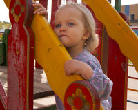 Girl looking aside above the wooden slide detail. Toddler girl looking aside above the wooden slide detail Stock Photo
