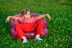 Girl looking aside in inflatable armchair Royalty Free Stock Photo