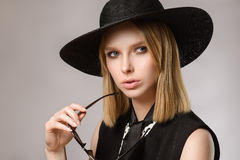 Girl looking away in hat keeps sunglasses near the face Royalty Free Stock Image