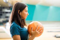 Girl Looking Away While Practicing Bowling In Club. E view of confident teenage girl looking away while practicing bowling in club stock images