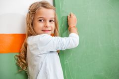 Girl Looking Away While Writing On Chalkboard In Stock Photos