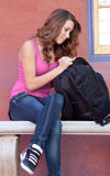 Girl looking in backpack Royalty Free Stock Photos