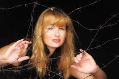 Girl looking through barbed wire Stock Photography