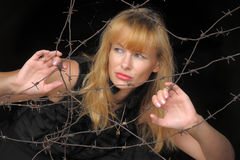 Girl looking through barbed wire Royalty Free Stock Photography