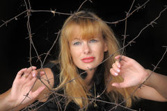 Girl looking through barbed wire Royalty Free Stock Photos
