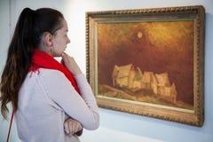 Girl looking at Bazovsky's painting, Slovakia stock photo