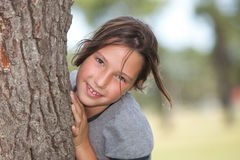 Girl looking from behind a tree Stock Images