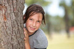 Girl looking from behind a tree. Portrait of a girl looking behind a tree stock images