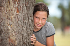 Girl looking from behind a tree. Portrait of a girl looking behind a tree stock photos